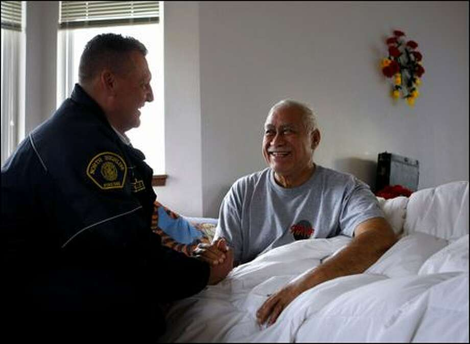 Dixie Crichton smiles earlier this month as he is visited by North Highline Fire District Chief Scott LaVielle at his home south of Seattle. Photo: Andy Rogers/Seattle Post-intelligencer Photos