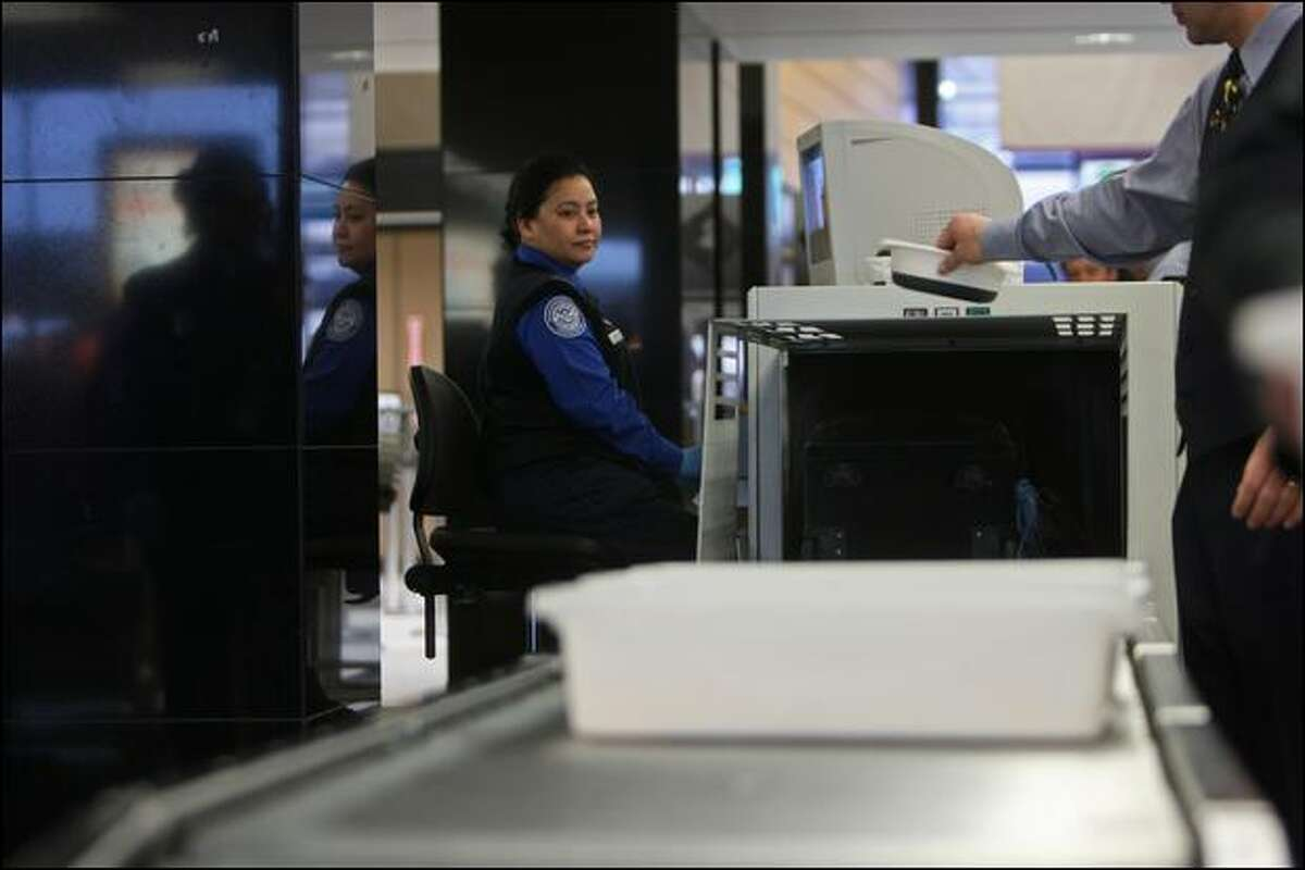 Angela Oliva, a Transportation Security Administration officer from Kent, operates the X-ray scanner on Christmas Eve at Sea-Tac Airport.