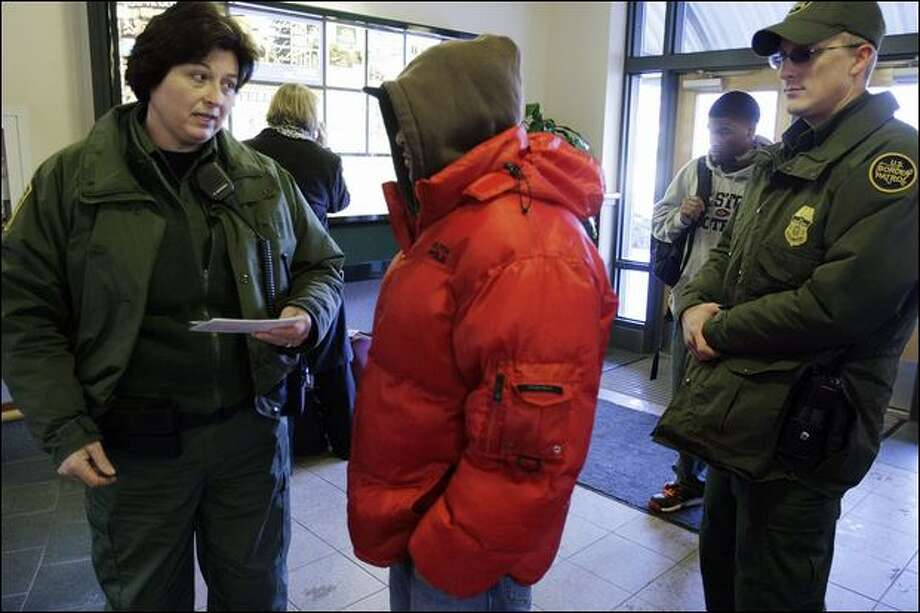 U.S. Border Patrol Agent Rebecca Moldenhauer talks with a man she detained at the Bellingham bus station Dec. 15 for being in the U.S. illegally. Agent John Colson is at right. Photo: Meryl Schenker/Seattle Post-Intelligencer