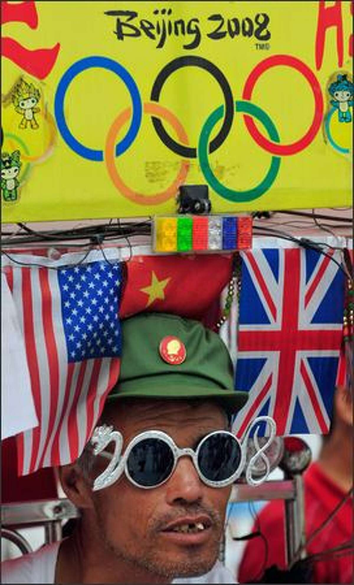 An Olympic fan rides his Olympic-decorated tricycle past the National Stadium, also known as the Bird's Nest, in Beijing. Fans will be unable to wave banners supporting national teams at the Beijing Olympics, according to an official guide book for spectators.