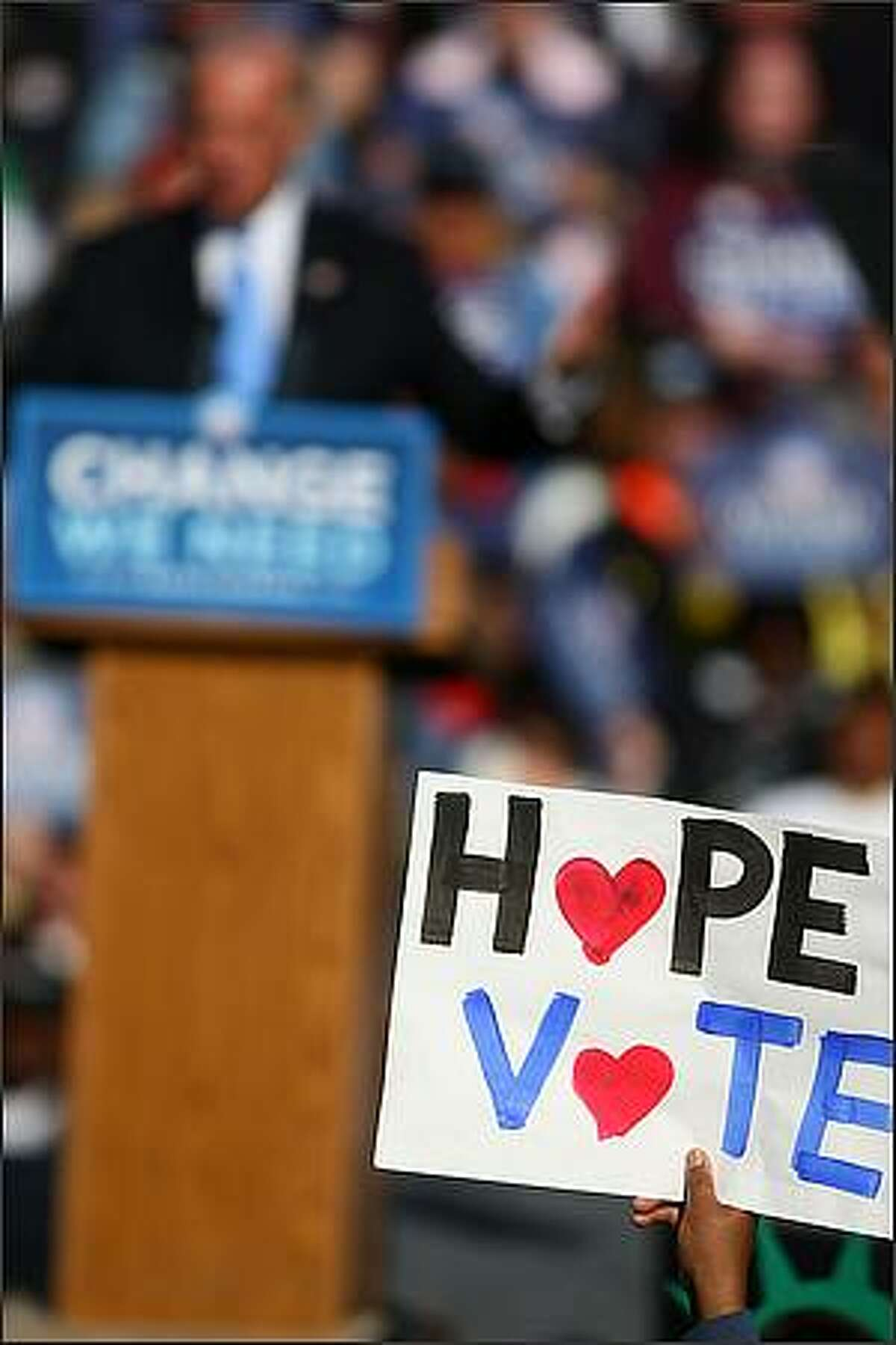 Democratic Vice Presidential candidate Joe Biden speaks on stage as a supporter holds a sign at Cheney Stadium in Tacoma.
