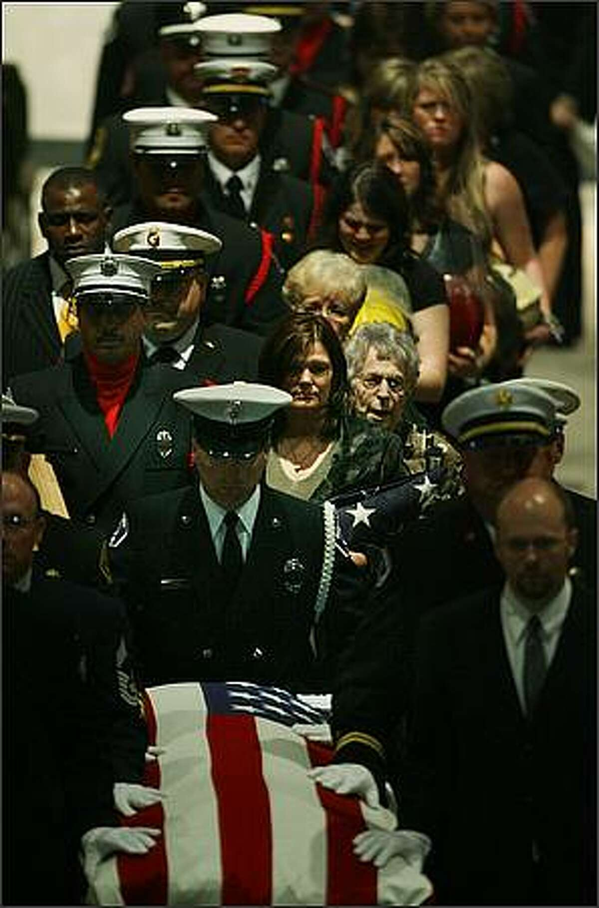 Marylee Packer (dark hair, center) and other family members follow the casket bearing Marylee's husband, East Pierce Fire and Rescue Fire Chief Dan Packer, who died July 26 fighting a California wildfire, at the conclusion of a memorial service held at Christian Faith Center in Federal Way on Thursday..