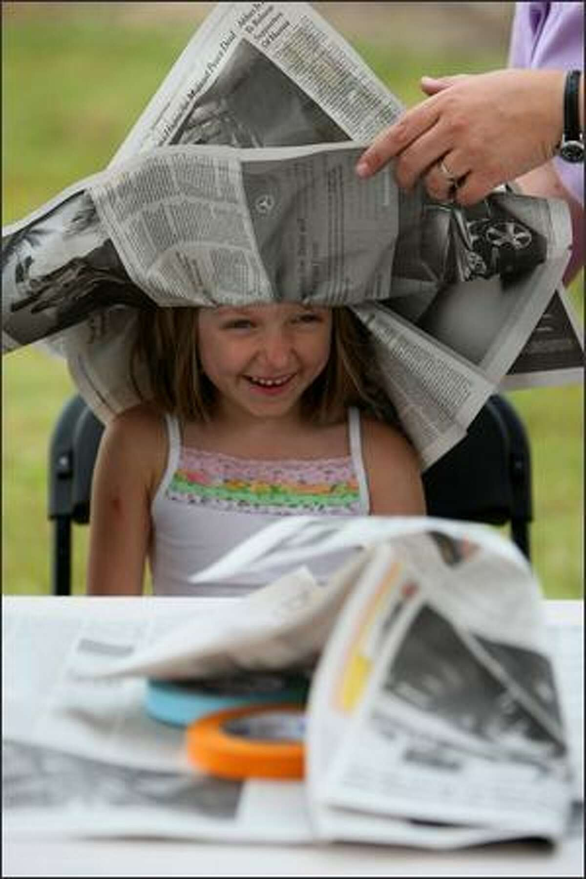 Kelly Blair of Seattle makes a newspaper hat during the Taste of Edmonds on Saturday. The festival features food booths, music and kids activities.
