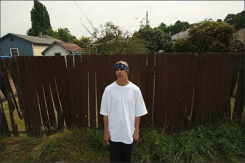 Danger, a member of a Sureno gang in Seattle, stands in an alley in South Park near his gang's main meeting house.