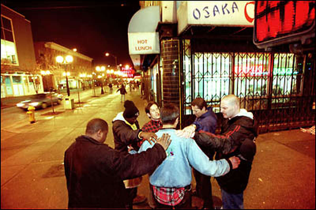 Members of the Victory Outreach Church place their hands on a man's shoulders and pray for him in downtown Seattle. Church members comb the streets on Tuesday evenings looking for addicts, gang members, prostitutes and anyone who might want a helping hand.