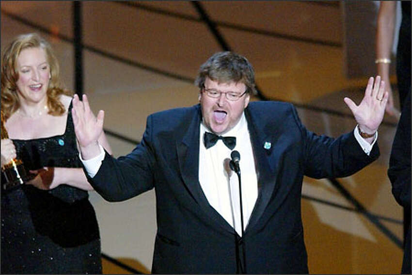 Director Michael Moore makes a statement after accepting his Oscar for best documentary feature for the film Bowling for Columbine during the 75th annual Academy Awards Sunday, March 23, 2003, in Los Angeles. At left holding the award is Kathleen Glenn.
