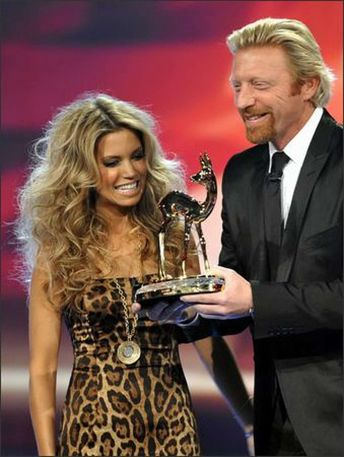 Dutch model Sylvie van der Vaart and former tennis champion German Boris Becker present a Bambi trophy.