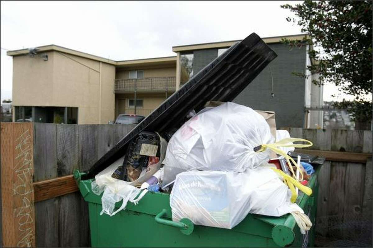 Garbage overflows from bins in front of an apartment building on 14th Avenue West in Seattle on Sunday.