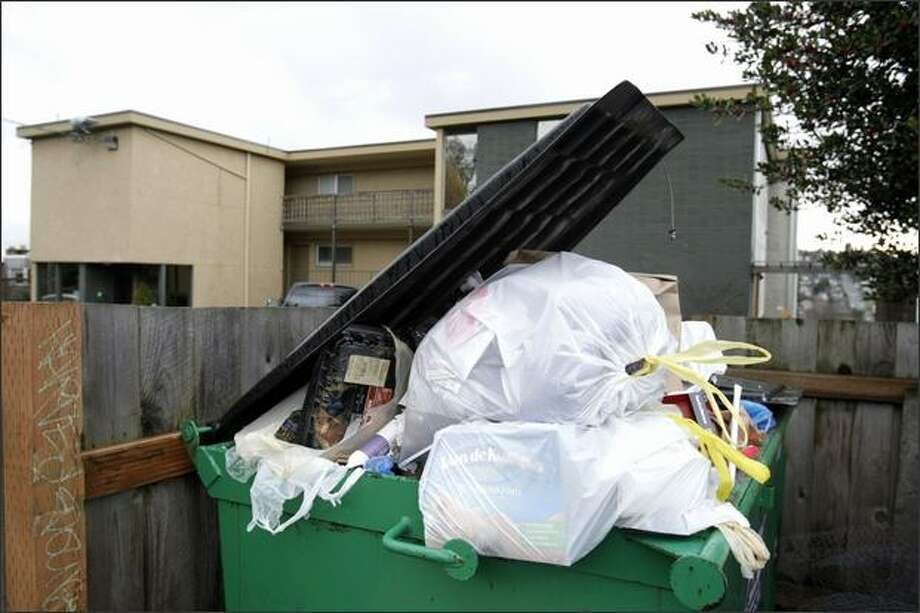 Garbage overflows from bins in front of an apartment building on 14th Avenue West in Seattle on Sunday. Photo: Meryl Schenker/Seattle Post-Intelligencer