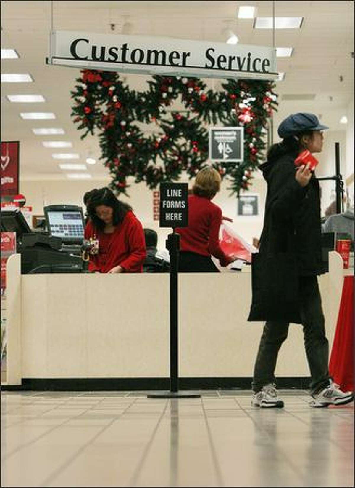 A sign shows where the line should start for a checkout counter and customer service station at JC Penney Northgate mall Friday, Nov. 28, 2008, in Seattle.