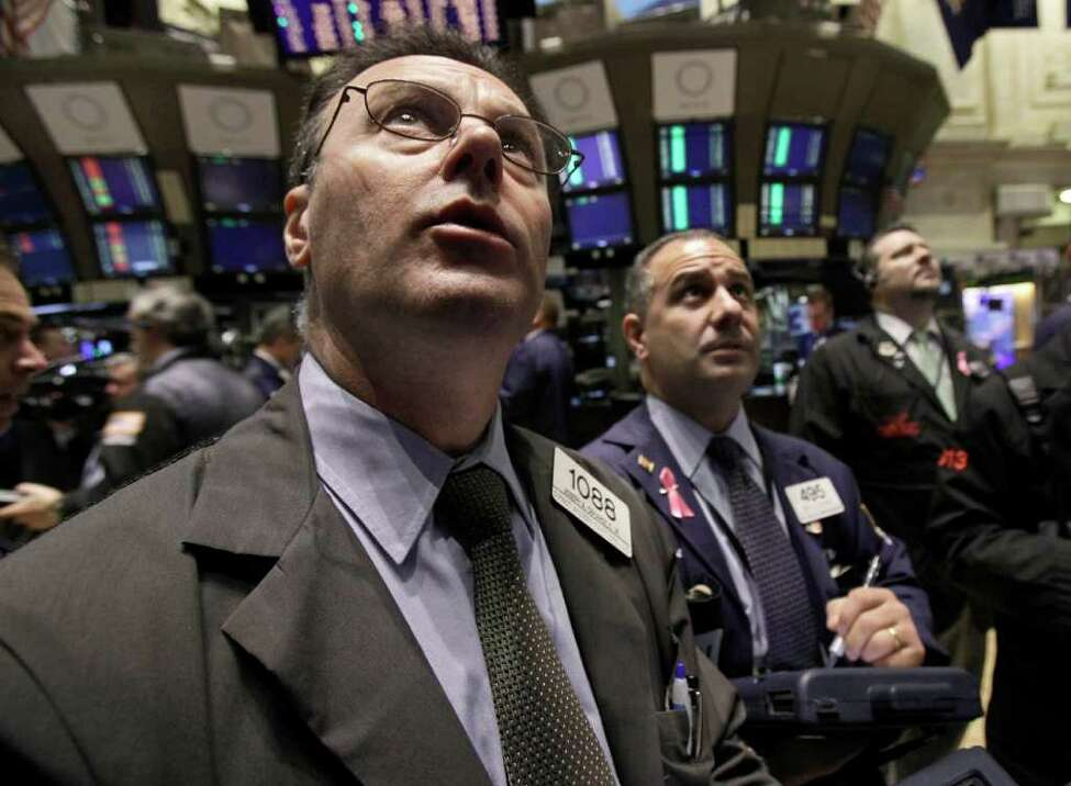 FILE - In this March 17, 2011 file photo, Joseph Tarangelo, left, checks prices with fellow traders as he works on the floor of the New York Stock Exchange. (AP Photo, file)