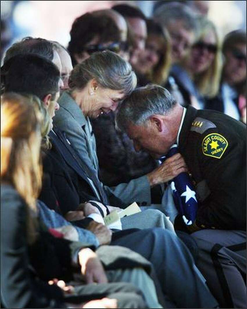 Skagit County Sheriff Rick Grimstead hands a flag over to Peggy Bengry, mother of Deputy Anne Jackson, during her memorial service.