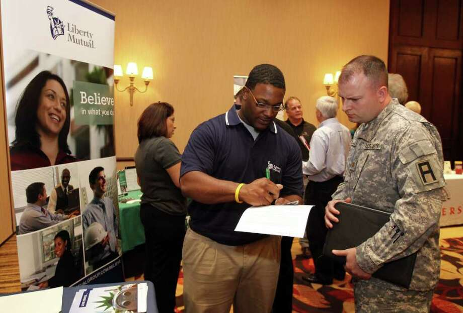 Army Major George Weilhamer, of Greenwood, Ind., talks with a recruiter from Liberty Mutual at a job fair in Indianapolis, Wednesday, March 23, 2011. Weilhamer is retiring from the Army in April. Fewer people applied for unemployment benefits last week, evidence that layoffs are slowing and employers may be stepping up hiring.(AP Photo/Michael Conroy) Photo: Michael Conroy