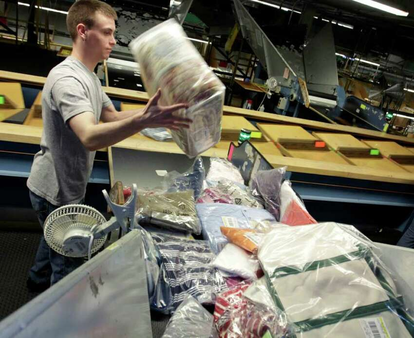 Justin Reil, of Brunswick, Maine, prepares merchandise for shipping at a facility at L.L. Bean in Freeport, Maine on Thursday, March 24, 2011. A spokesman at the outdoors and clothing retailer announced that the company is offering permanent, no-strings-attached free shipping. (AP Photo/Pat Wellenbach)