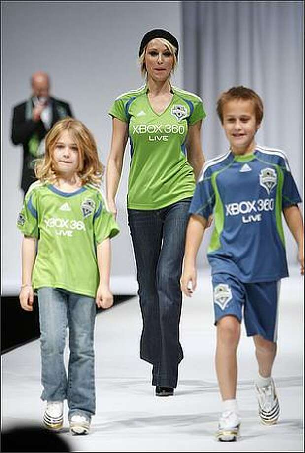Actress Josie Bissett and children Maya and Mason, model the Seattle Sounders FC home (green) and away (blue) jerseys during a runway fashion show featuring Sounders clothing at the WaMu Theater in Seattle. Photo: Mike Urban, Seattle Post-Intelligencer