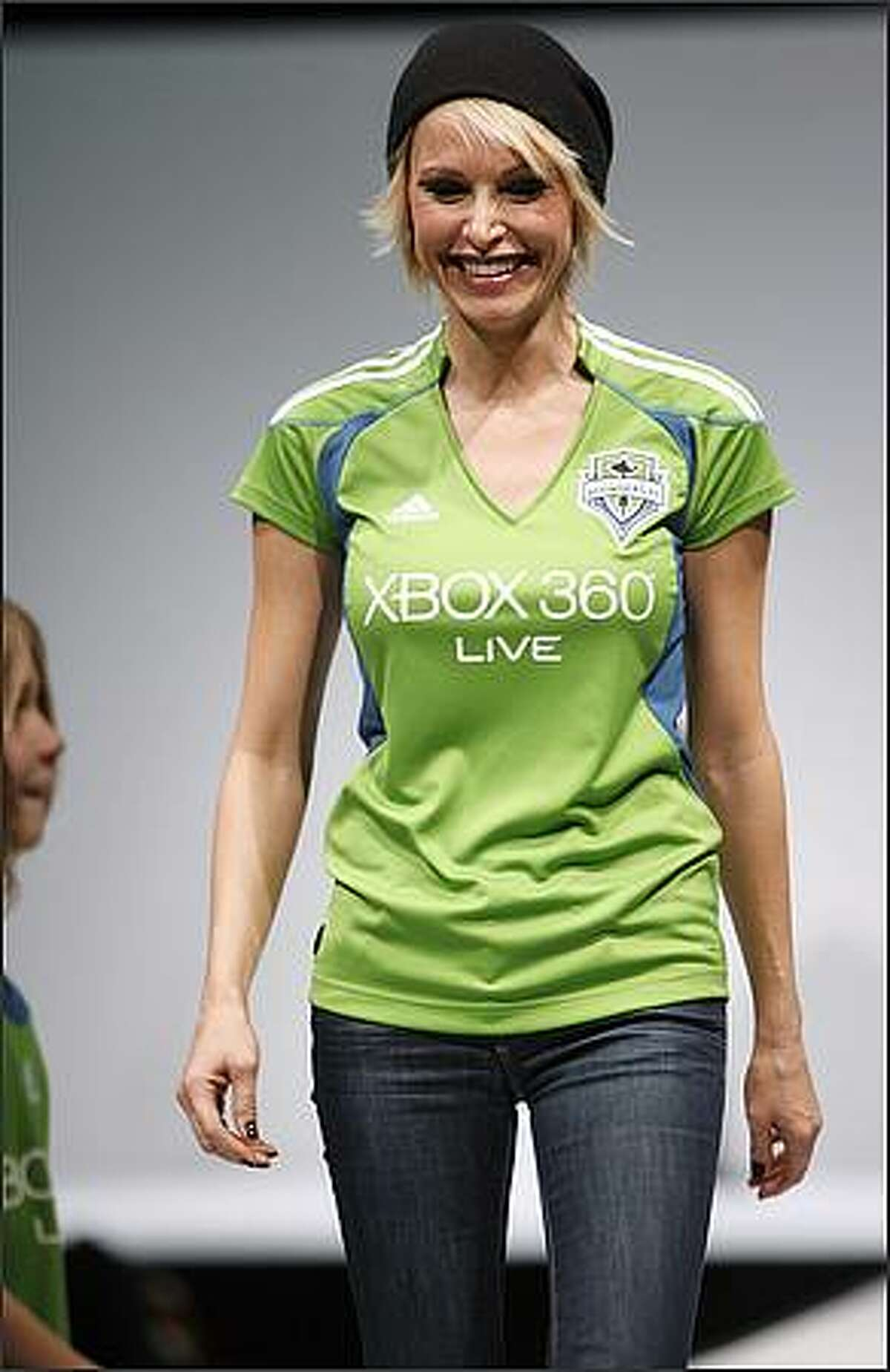 Actress Josie Bissett models the Seattle Sounders FC home jersey during a runway fashion show featuring Sounders clothing at the WaMu Theater in Seattle.