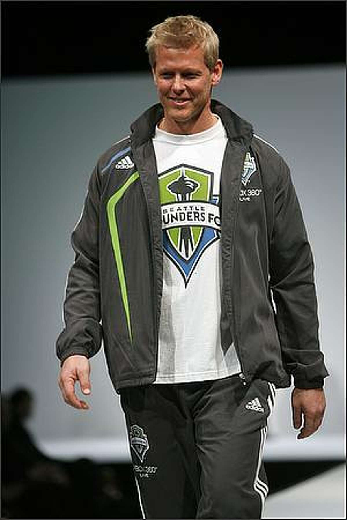 Model Dave wears the Seattle Sounders FC presentation suit during a runway fashion show featuring Sounders clothing at the WaMu Theater in Seattle.