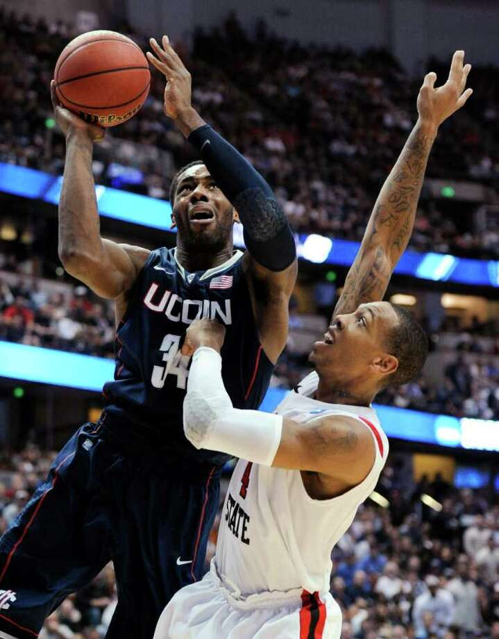 Connecticut's Alex Oriakhi (34) drives past San Diego State's Malcolm Thomas (4) during the first half of a West regional semifinal in the NCAA college basketball tournament, Thursday, March 24, 2011, in Anaheim, Calif. (AP Photo/Mark J. Terrill) Photo: AP