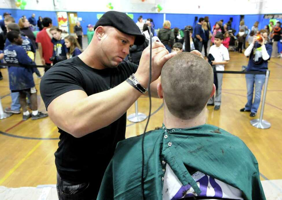 Barber Benjamin Pratt, owner of Giovanni George, center, shaves Glenn Westfall of Colonie on Thursday, March 24, 2011, at Latham Ridge Elementary School in Latham, N.Y. Children and adults had their heads shaven to benefit St. Baldrick's Foundation, which gives grants for childhood cancer research. (Cindy Schultz / Times Union)