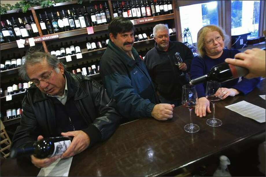Luthra Narinder, left, of Woodinville examines a bottle of wine as Rich Kiepke and Judy Thomas, also of Woodinville, wait for a fill-up at Village Wines. Peter Byass, visiting from Australia, stands in the back. Photo: Andy Rogers/Seattle Post-Intelligencer