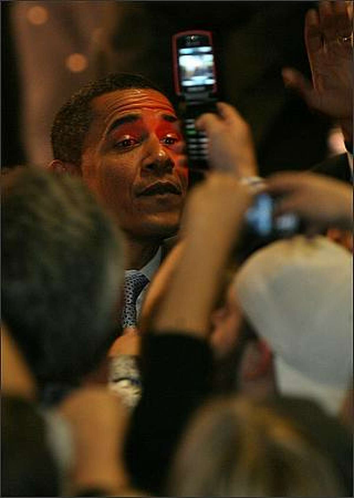 Tuesday Dec. 11, 2007. Sen. Barack Obama is illuminated by a camera phone as he shakes hands with the audience after speaking at a fundraising event held at the Showbox Sodo club in Seattle.