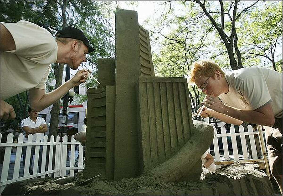 Mat Johnson (left) and Drew Kirkpatrick use straws to blow away sand while making a sculpture with other employees of Magnusson Klemencic Associates, a Seattle structural and civil engineering firm, in preparation of Seattle Sandfest at the Westlake Plaza in downtown Seattle.