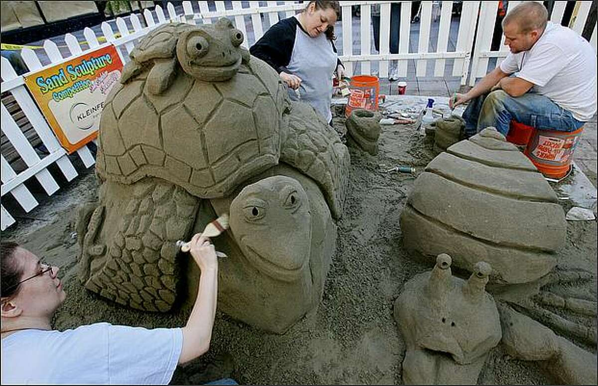 """Tiffany Kreider (from left), Diane Levy and Ryan Hogg work on sculpture entitled """"Underwater City"""" during the Seattle Sandfest."""