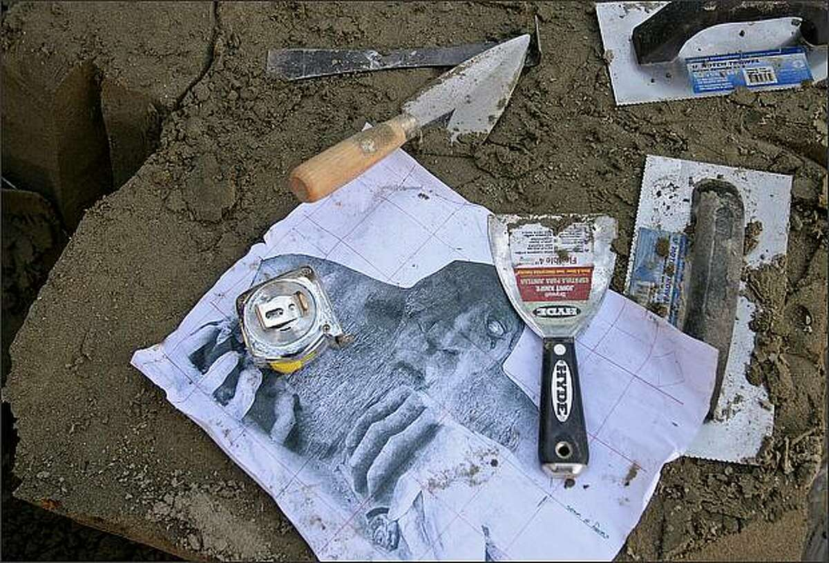 A drawing of the Fremont Troll, along with tools of the trade, were on hand as the team from the Big Brothers Big Sisters of Puget Sound worked on a sculpture of the local landmark.