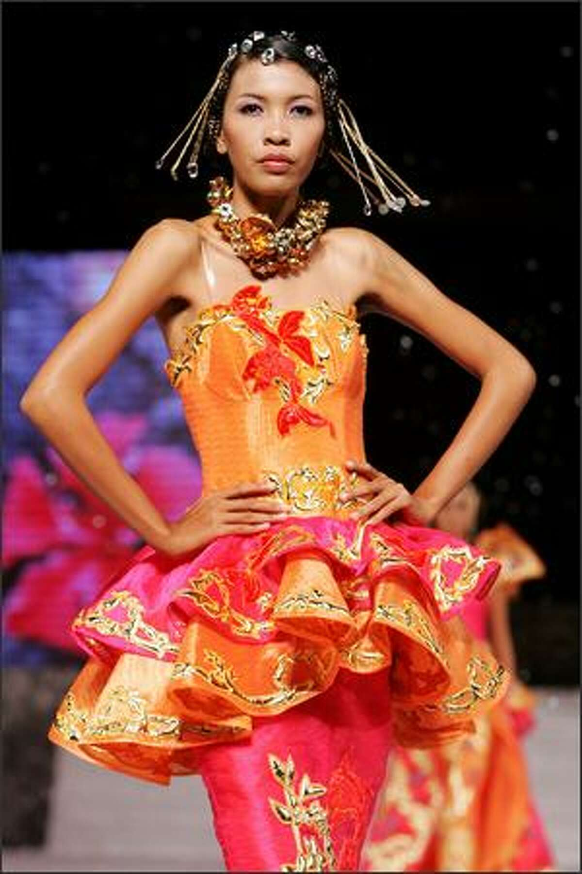 A model showcases designs by Korean couture designer Andre Kim at the opening catwalk show on the first day of Bali Fashion Week 2008 at the Lotus Pond, Garuda Wishnu Kencana on Monday in Jimbaran, Bali, Indonesia.