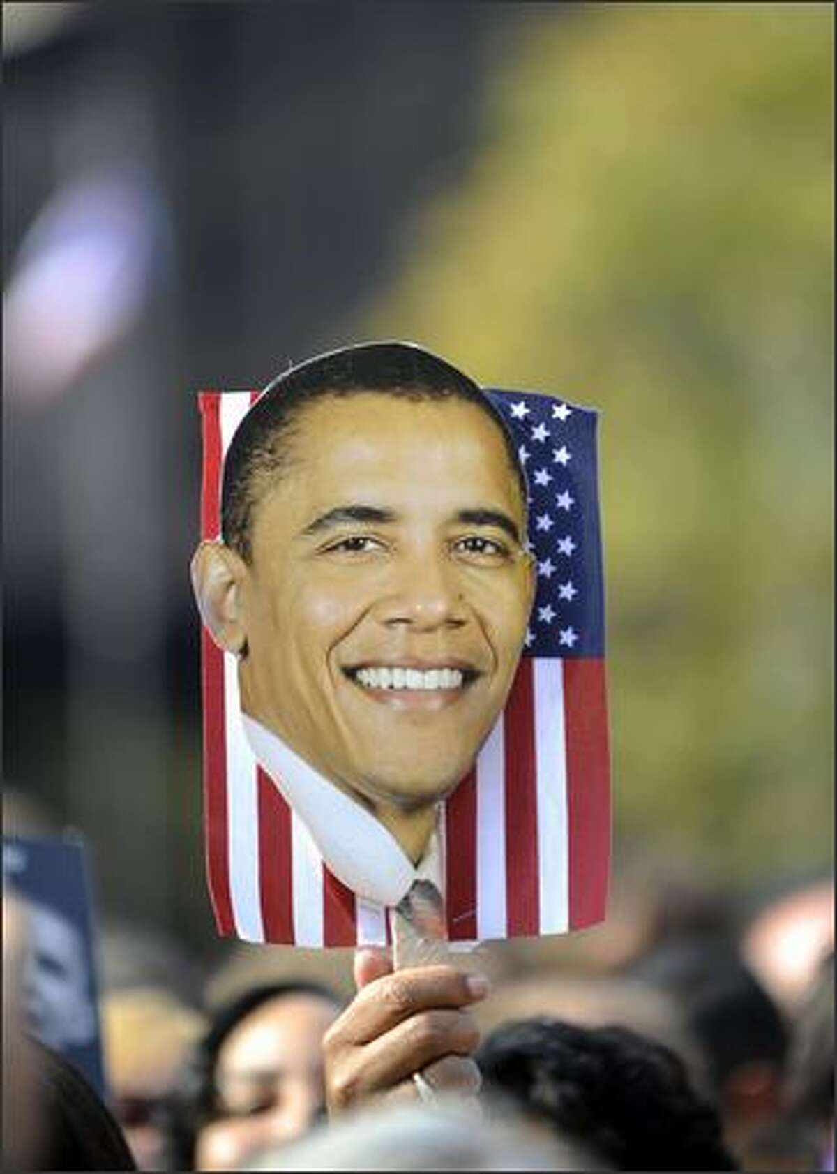 A supporter of Democratic presidential candidate Illinois Senator Barack Obama holds a U.S. flag and a picture of Obama during a rally at Ohio State House in Columbus, Ohio, on Sunday.