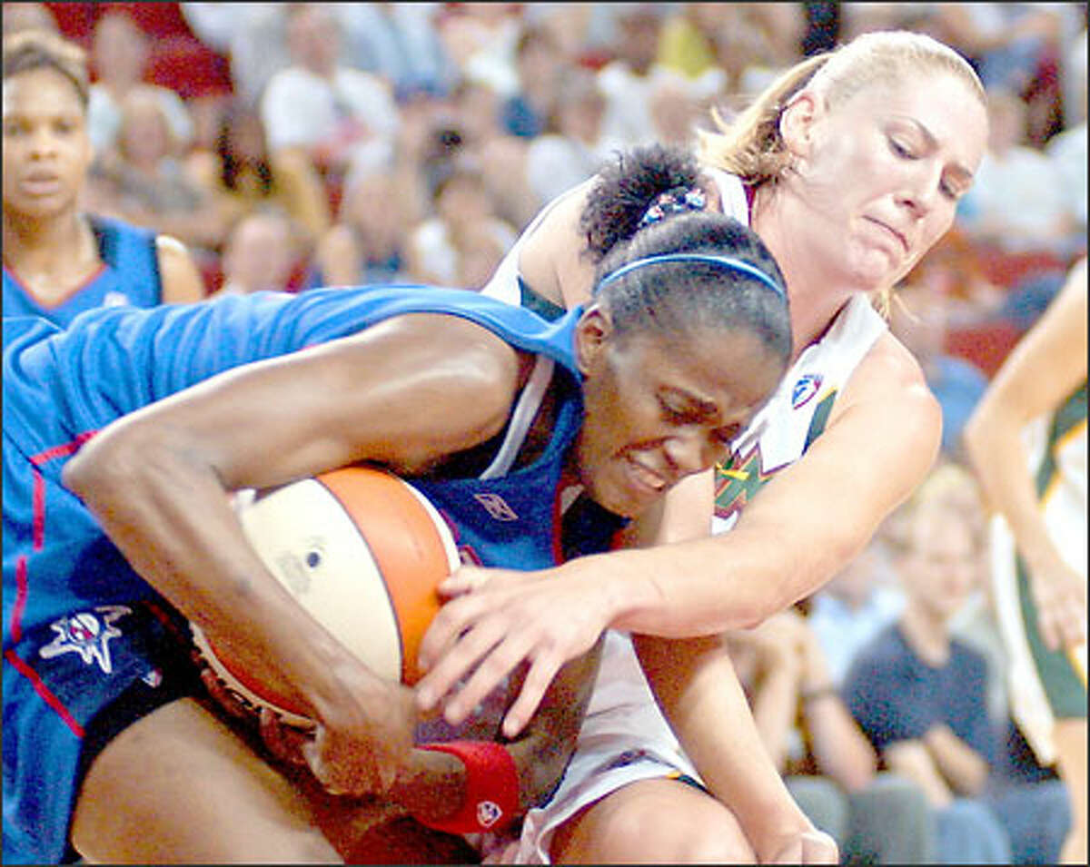 Detroit's Swin Cash keeps the ball away from Seattle's Lauren Jackson during the second half.