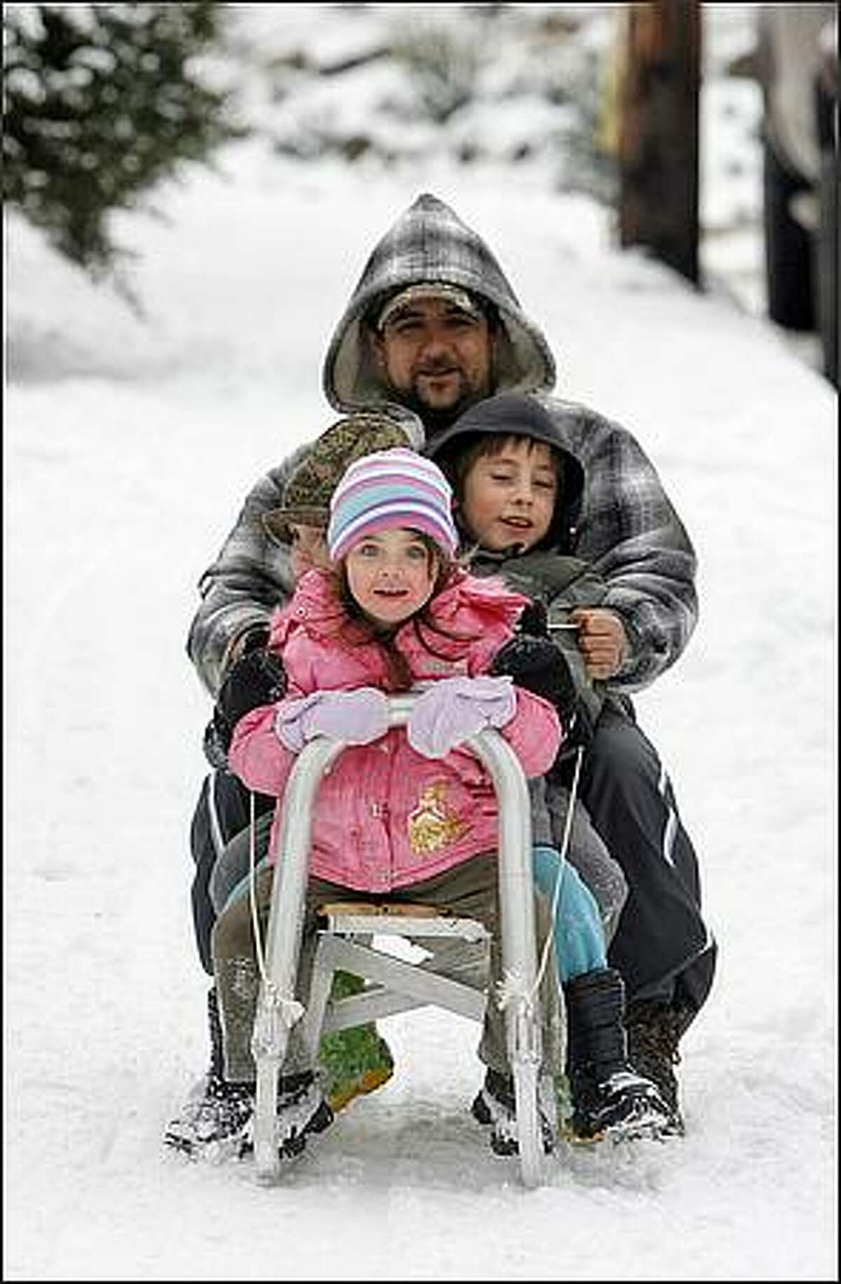 Zsolt Prepuk, a welder and metal fabricator, slides down SW Wildwood Place in Seattle, with his son, Attila Prepuk (right), 7, daughter Anita Prepuk (front), 3, and neice Eliza Gorog (left), 3, on a