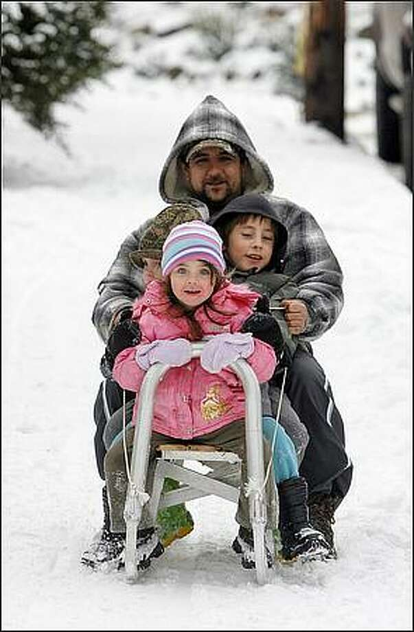 "Zsolt Prepuk, a welder and metal fabricator, slides down SW Wildwood Place in Seattle, with his son, Attila Prepuk (right), 7, daughter Anita Prepuk (front), 3, and neice Eliza Gorog (left), 3, on a ""slanko,"" Hungarian for sled, that he fabricated for his children. Photo: Mike Urban, Seattle Post-Intelligencer"