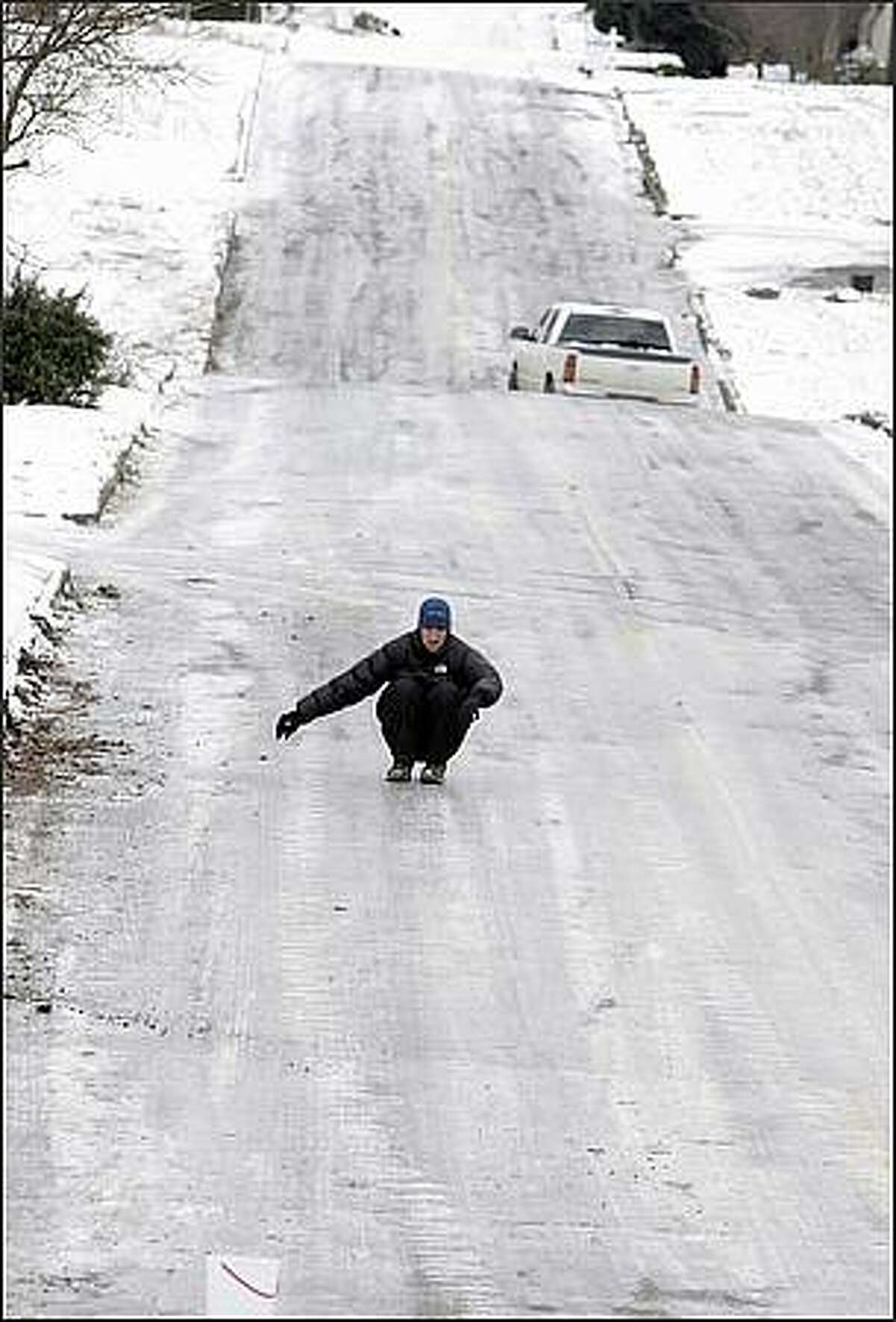 Josh Byeman slides down W Dravus Street on his way to the store.