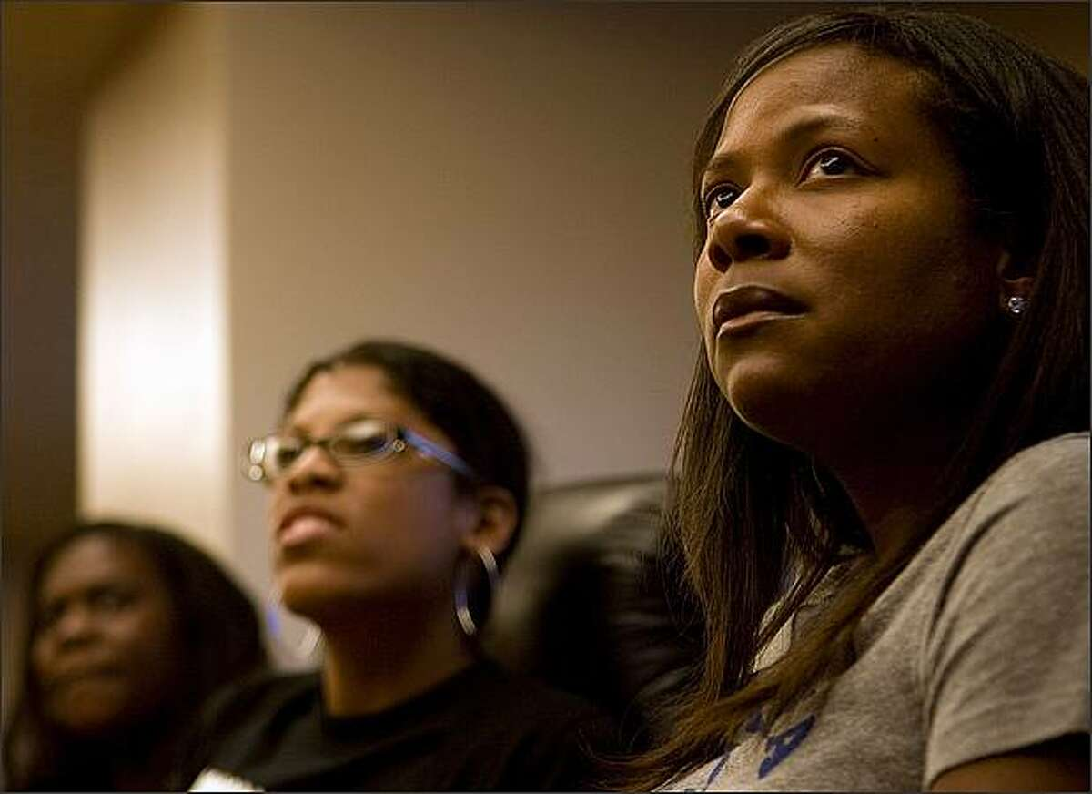 Listening, from right, Dana Chenevert, Jacqueline Justice, and Jamila Taylor with the Urban League, gather at Crown Plaza Hotel to watch Barack Obama's nomination speech.