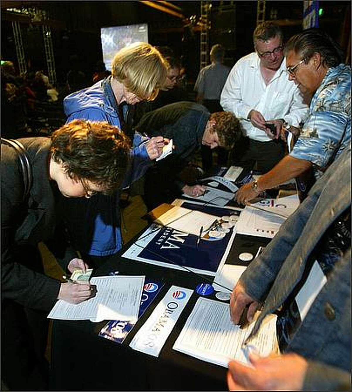 Rebecca Partington from Seattle (left front) signs up to receive bumper stickers. Senator Obama's Campaign for Change hosts a party at the Showbox SoDo in Seattle for supporters to watch his speech on TV, broadcast from the National Democratic Convention in Denver, CO.