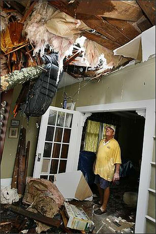 Richard Bezet looks over damage to the living room of his Baton Rouge, La., home after a tree fell through the roof due to winds from Hurricane Gustav. Kathy Anderson/AP/The Times-Picayune