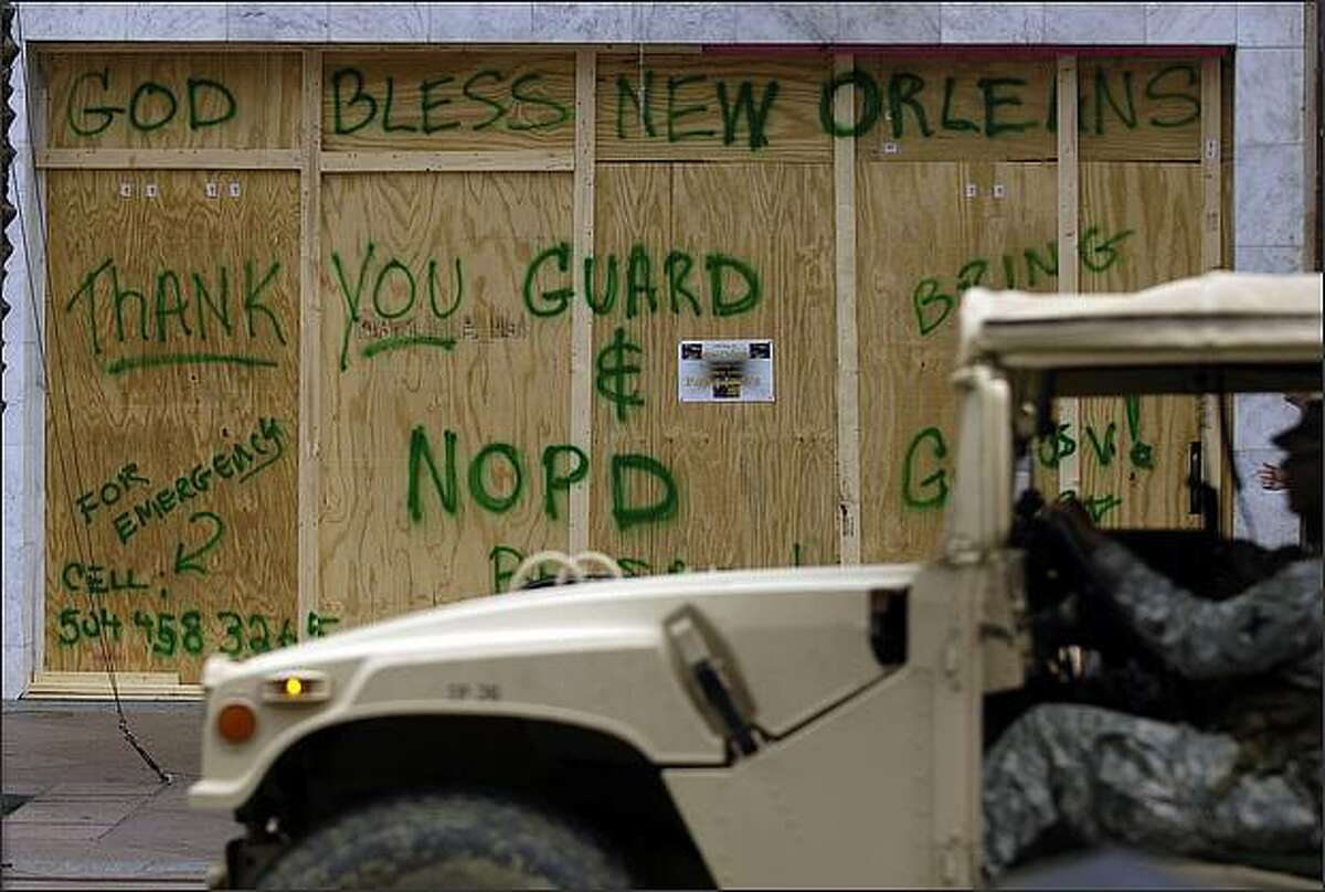 A Louisiana National Guard vehicle passes a boarded up store front on Canal Street in New Orleans, Louisiana. Stephen Morton/Getty Images