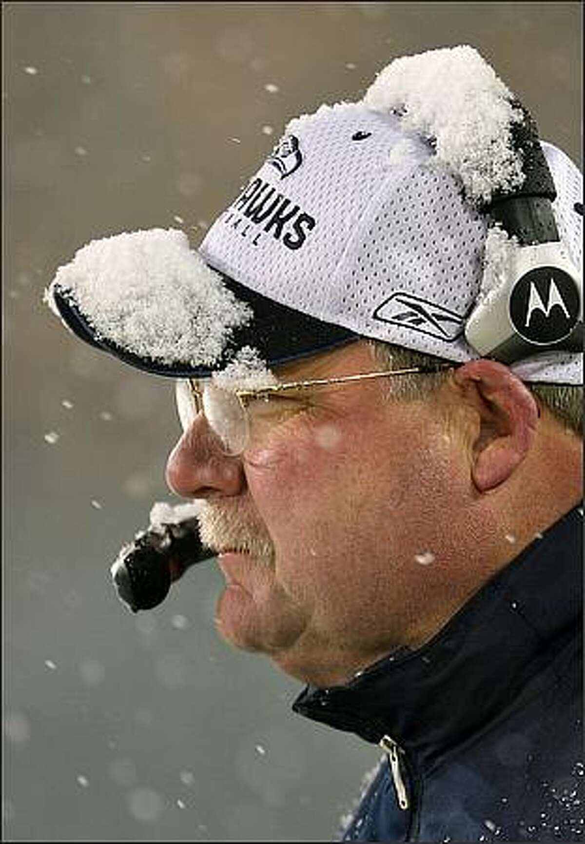 Seattle Seahawks head coach Mike Holmgren watches the final monets of the fourth quarter fade with a layer of snow on the brim of his cap and headphones as the Seahawks lose to the Green Bay Packers at Lambeau Field in Green Bay, Wisconsin., Saturday. Jan. 12, 2007. (Seattle Post-Intelligencer/Mike Urban)