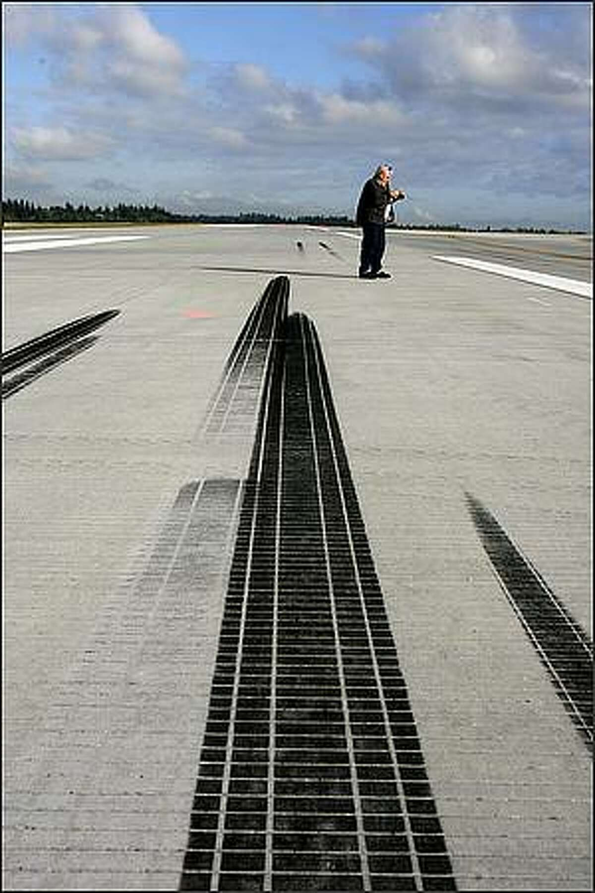 Dennis Franks, an FAA inspector looks over skid marks left by the wheels of a Northwest Airlines A330 wide-body after it performed a touch and go landing on October 8, 2008.