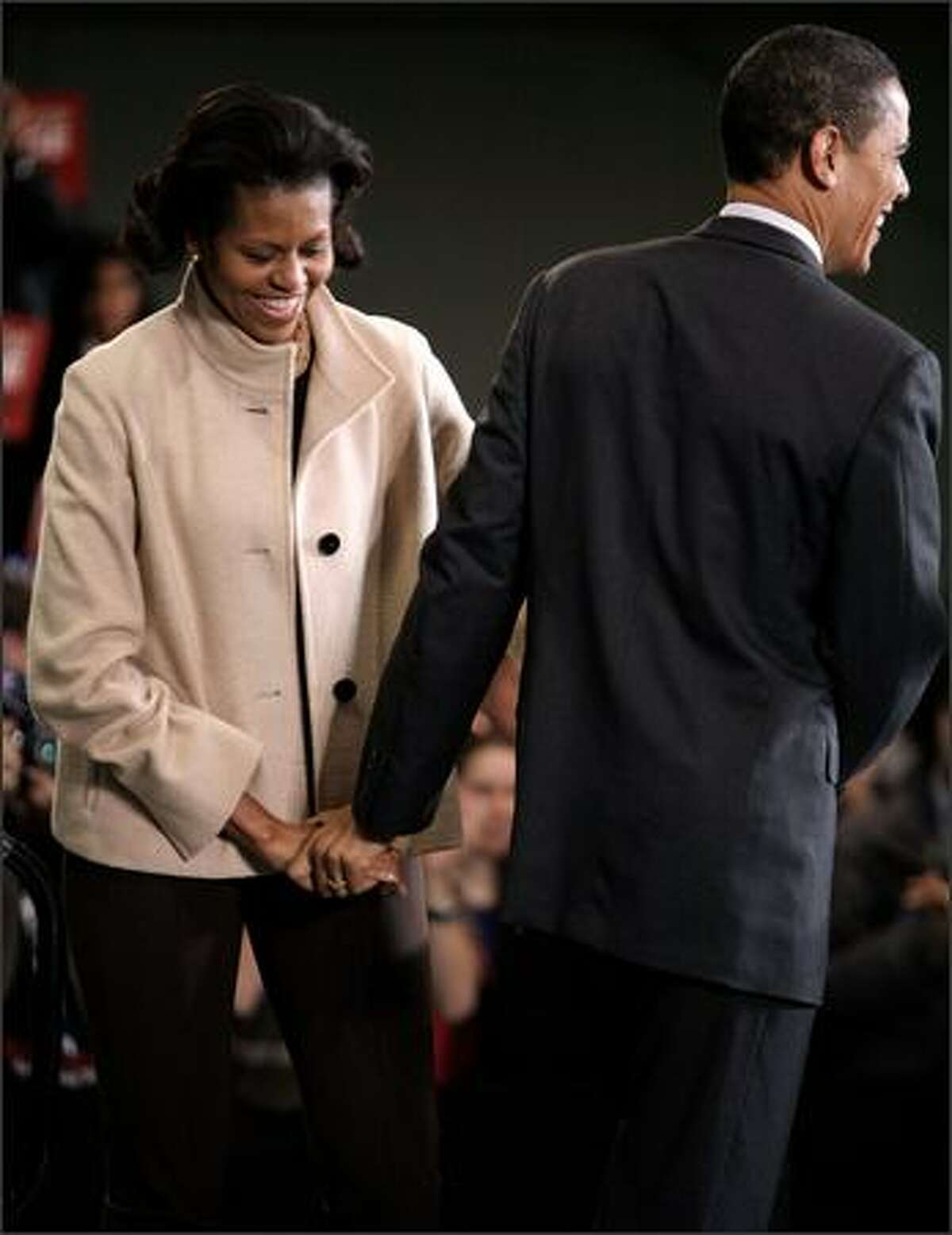 Democratic presidential hopeful Sen. Barack Obama (D-IL) (R) holds hands with his wife Michelle Obama during a rally at the athletics facility at Dartmouth College Jan. 8, 2008 in Hanover, New Hampshire. Polls show Obama leading Sen. Hillary Clinton (D-NY) moving into today's New Hampshire primary.