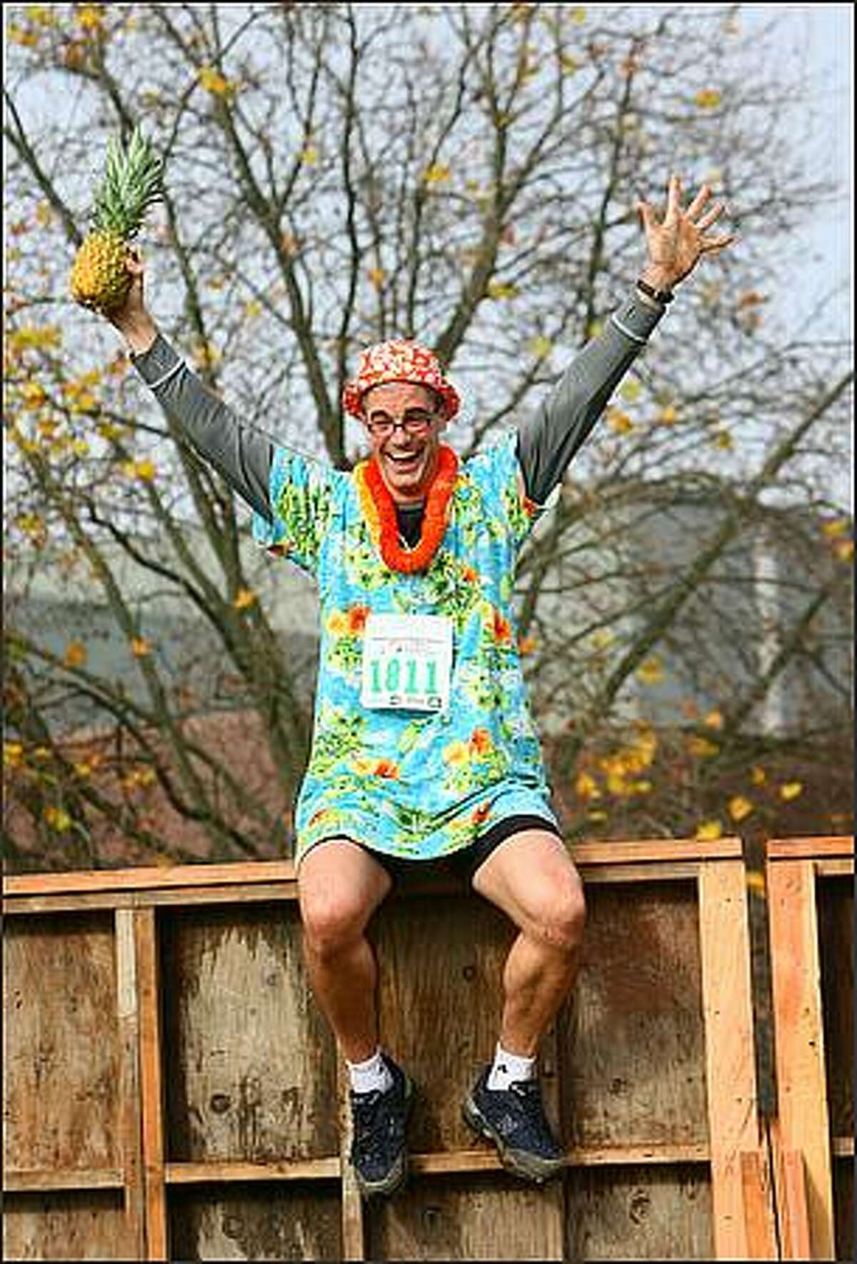 Ted Mandelkorn raises his arms as he summits an obstacle during The Winter Pineapple Classic, a 5k run and obstacle course, at Magnuson Park in Seattle. The race attracted over 3,000 runners who, as members of their respective teams, completed the course carrying pineapples. Many of the participants dressed up in goofy Hawaii-themed costumes. Proceeds from the event go toward The Leukemia and Lymphoma Society's mission to fund cancer research and assist patients and families fighting blood cancers.