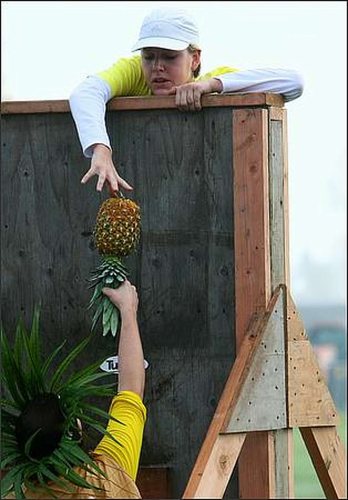 Participants pass a pineapple over an obstacle during The Winter Pineapple Classic.