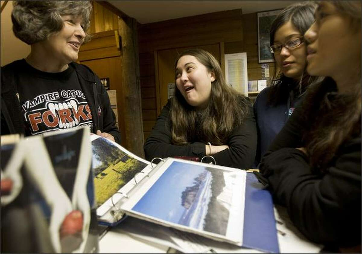 """From left, Chamber of Commerce volunteer Marcia Yanish talks with Crystal Bowhall, Masami Araki, and Kelly Fujio before the three head out to find the many different """"Twilight"""" spots on Nov. 7, 2008, in Forks, Washington. The three made a quick day trip over to Forks from Bremerton where they were in town for a friends wedding on Saturday."""