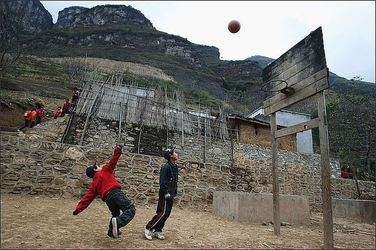 Students play basketball at their school in the village of Gulucan in Hanyuan county, Sichuan province, China. More than 60 farmers' families live in six isolated locations, perched high above a spectacular canyon in the area. Some farmers' children have to walk three hours to their school along the edge of a crumbling, narrow mountain path with a sheer 5,000ft drop on one side.