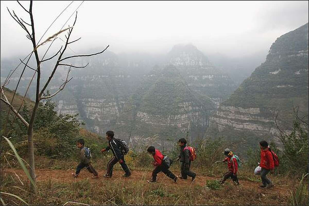Schoolboys walk to their school in the village of Gulucan in Hanyuan county, Sichuan province, China. More than 60 farmers' families live in six isolated locations, perched high above a spectacular canyon in the area. Some farmers' children have to walk three hours to their school along the edge of a crumbling, narrow mountain path with a sheer 5,000ft drop on one side.