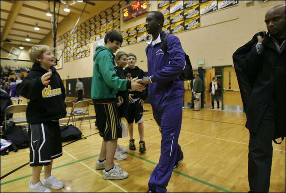Garfield High sophomore Tony Wroten is greeted by Inglemoor fans, from left, Andy Nelson, 12, Jackson Gardner, 12, Austin Fothergill, 11, and Chandler Edlin, 12, on Tuesday night. Photo: Gregory Shamus/Nbae/Getty Images