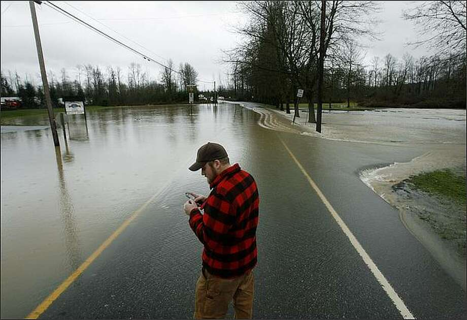 Jeff Rau of Carnation stopped to photograph the flooded Tolt River where SR 203 was closed just north of the river in Carnation, WA on Wednesday. Photo: Dan DeLong/Seattle Post-Intelligencer