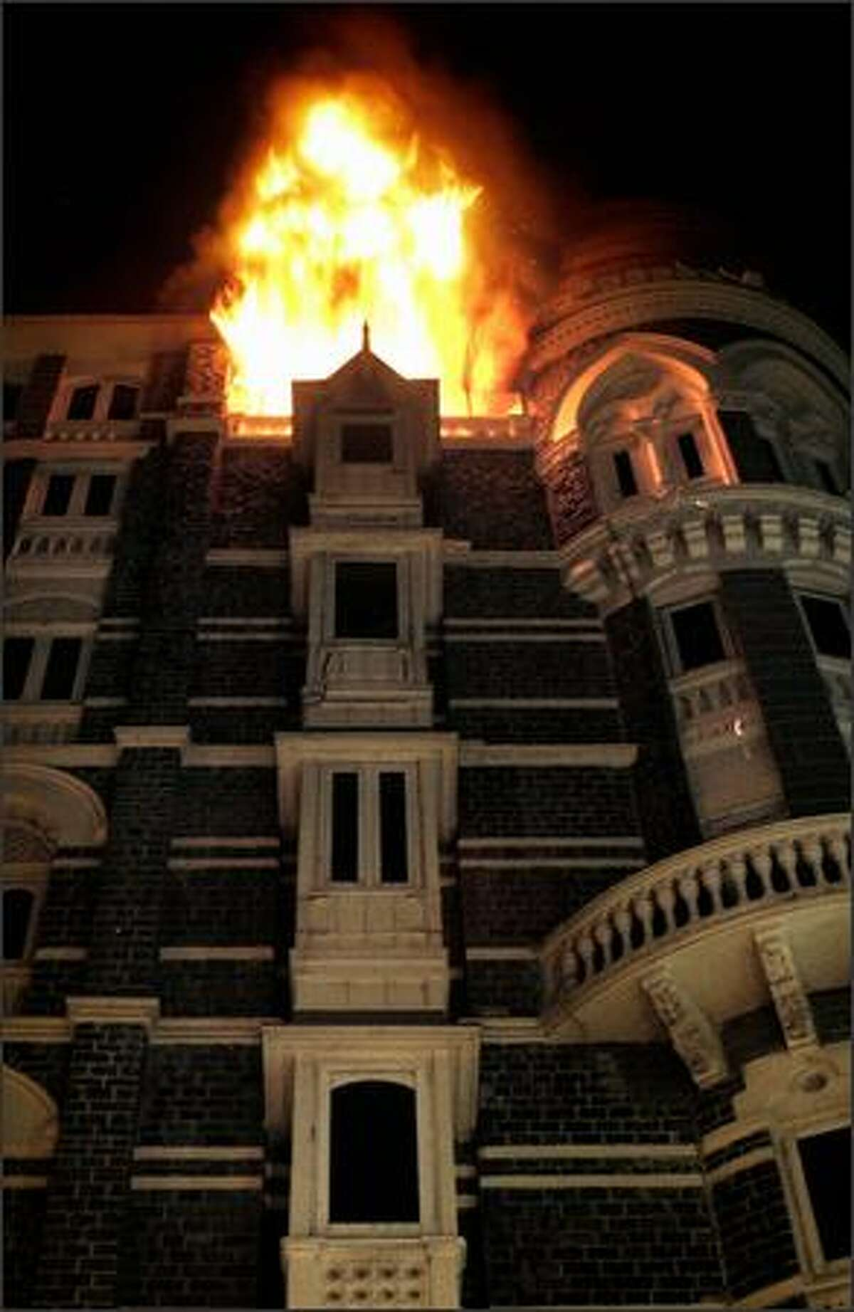 Fire engulfs the top floor of the Taj Mahal hotel, site of one of the shootouts with terrorists.