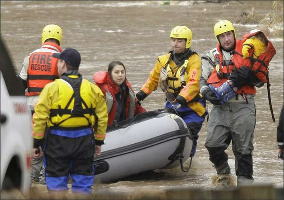 Rescue workers evacuate residents from a flooded neighborhood along McCutcheon Rd. near Orting, Wash. Wednesday. The rapidly rising Puyallup River forced hundreds of people in the area from their homes. (AP Photo/Ted S. Warren) Photo: / Associated Press